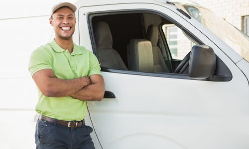Three quarter length portrait of smiling man standing against delivery van